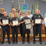 ouncil recognizes polices officers who received Lifesaving Awards.  Front, l to r:  MPO Michael Apgar, Officer Irelisse Fernández, MPO Michael Eppard, MPO Gerald Potts and Chief James Craze. Back, l to r: Mayor Emmett Jordan, Councilmembers Silke Pope, Edward Putens, Leta Mach, Judith Davis, Konrad Herling and Rodney Roberts.  Photo by Beverly Palau