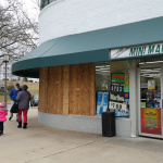 The windows are boarded up at the Mini Mart after a break in.