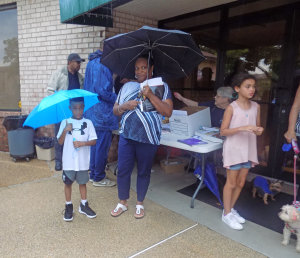 """Ryan Mitchell and mom Regina keep dry while eating ice cream. He said the best part of the evening is """"the police and meeting the mayor."""""""